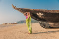Young woman in indian sari traditional posing front of old fisherman boat at india state goa Stock Photos