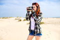 Young woman with instant photo camera on the beach Stock Photos