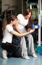 Young woman and instructor in the gym Royalty Free Stock Photos