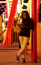 Young woman with ipad at theme park a working as a freelancer is browsing on her while reclining against a pillar in a the y Royalty Free Stock Image