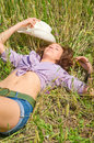 The young woman in jeans shorts lies in the field. Stock Photography