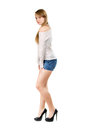 Young woman in jeans shorts wearing blue white blouse and black shoes isolated Royalty Free Stock Image