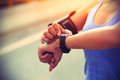 Young woman jogger ready to run set and looking at sports smart watch checking performance or heart rate pulse trace sport Stock Photography
