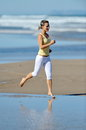 Young woman jogging on the beach in summer healthy Stock Images