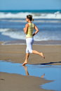 Young woman jogging on the beach in summer healthy Royalty Free Stock Images