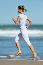 Young woman jogging on the beach in summer sunny day Royalty Free Stock Photography