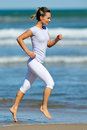 Young woman jogging on the beach in summer sunny day Royalty Free Stock Photos