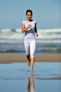 Young woman jogging on the beach in summer sunny day Stock Photo