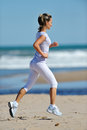 Young woman jogging on the beach in summer sunny day Stock Images