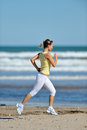 Young woman jogging on the beach in summer sunny day Royalty Free Stock Image