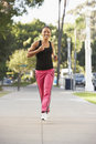 Young Woman Jogging On Street Stock Photography