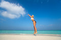 Young woman jumping on the beach, catch cloud Royalty Free Stock Photo
