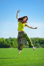 Young woman jumping on a green meadow beautiful jumpimg Stock Photo