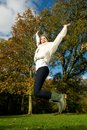 Young woman jumping for joy outdoors on a beautiful fall day portrait of Stock Photos