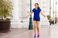 Young woman jumping a rope cute as part of her workout in the city Royalty Free Stock Photos