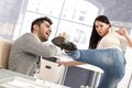 Young woman kicking boyfriend couple fighting women man relationship crisis stress at workplace Stock Images
