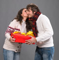 Young woman kissing a man with a present box women men on gray background Royalty Free Stock Photos
