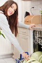 Young woman in kitchen doing housework. Stock Images