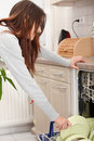 Young woman in kitchen doing housework. Royalty Free Stock Photography