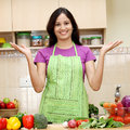 Young woman in kitchen excited standing with open palms Stock Images
