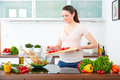 Young woman in the kitchen prepare salad ii with tomatoes and pepper Royalty Free Stock Photography