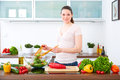 Young woman in the kitchen prepare salad vii smiles into camera Stock Photos