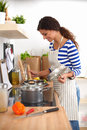 Young woman in the kitchen preparing a food isolated Stock Images