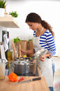 Young woman in the kitchen preparing a food isolated Stock Photo