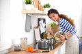 Young woman in the kitchen preparing a food isolated Stock Photography