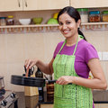 Young woman in kitchen smiling indian with utensils Stock Photo