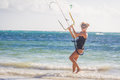 Young woman kite surfer getting ready for kiting on sand tropica Royalty Free Stock Photo