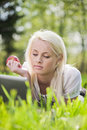 Young woman with laptop lying on the grass Stock Image