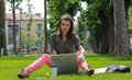 Young woman with a laptop in the park working on outside an urban Stock Photos