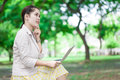 Young woman with laptop sitting on bench and looking to sky Royalty Free Stock Image