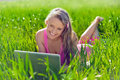 Young woman with laptop sitting on green grass Royalty Free Stock Photos