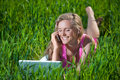 Young woman with laptop sitting on green grass Royalty Free Stock Images