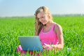 Young woman with laptop sitting on green grass Stock Photography