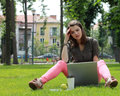 Young woman with laptop thinking in front of a outside in an urban park Royalty Free Stock Photos