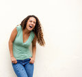 Young woman laughing against white background portrait of a Stock Images