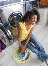 Young woman with laundry basket portrait of african american sitting at laundromat Royalty Free Stock Photography