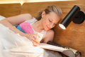 Young woman laying in bed reading a magazine pretty with white sheets and Stock Photo