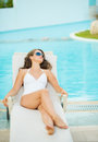 Young woman laying on chaise longue at poolside with long hair Royalty Free Stock Images