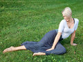 Young woman laying on the green grass Royalty Free Stock Images