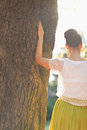 Young woman lean against tree. Rear view Stock Photo