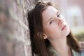 Young woman leaning against brick wall close up portrait of a cute outdoors Stock Photography