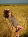 Young woman leaning hay stack enjoying breeze Royalty Free Stock Photo