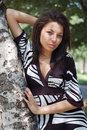 Young woman leaning on tree Stock Photo