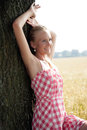 Young woman leaning on a tree pretty with blond hair against she is visibly relaxed Royalty Free Stock Photos