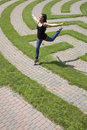 Young Woman Leaping Over a Grass Maze Royalty Free Stock Photos