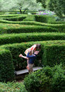 Young woman leaps in her fiance s arms women into the of a garden maze Royalty Free Stock Photo